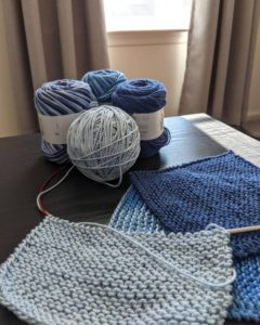 Four skeins of blue yarn on a table with 3 knit washcloths, one of which is in progress. A sunny window with grey curtains shines in the background.