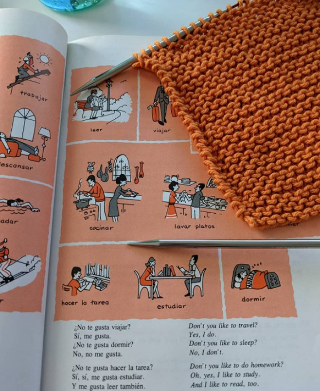 Image of a 1980's era Spanish textbook and a knit washcloth