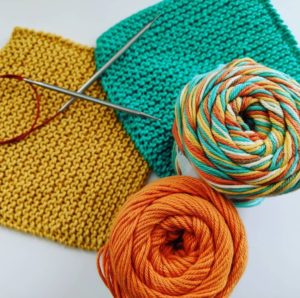 Photo: One yellow and one green washcloth, along with a set of circular knitting needles, and skeins of orange and multicolor cotton yarn.