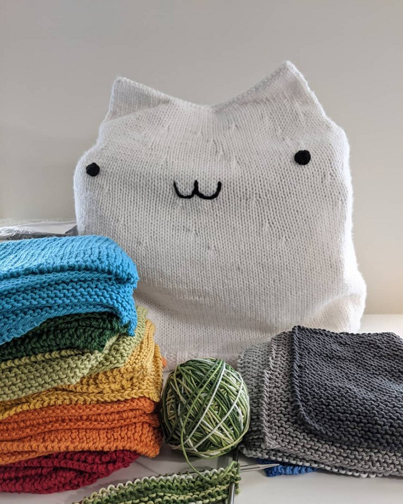 Two piles of colorful knitted washcloths stacked in front of a white knitted Bongo Cat cover which protects the sewing machine beneath it.