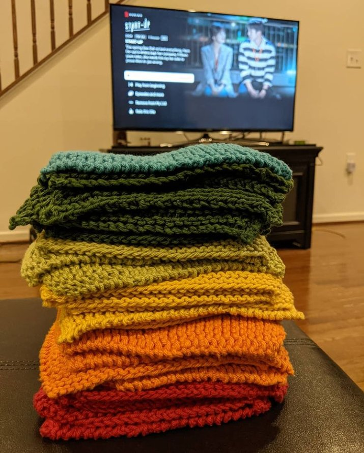 "A stack of knit cloths, blue to red, stacked on a surface in front of a flat screen TV showing the Netflix interface, with the show ""Start Up"" on the screen."