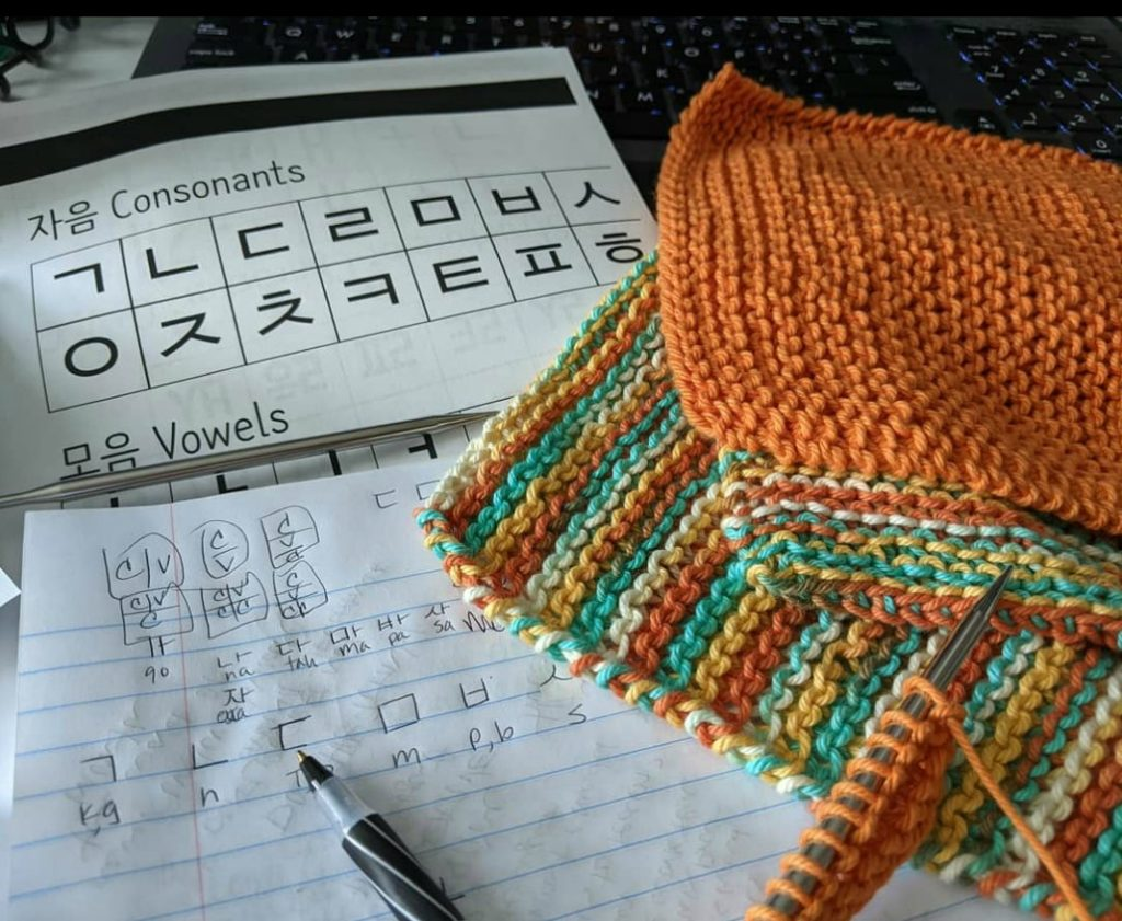 Bright hand knitted washcloths sitting next to a notebook and paper handouts with Korean letters printed on them.