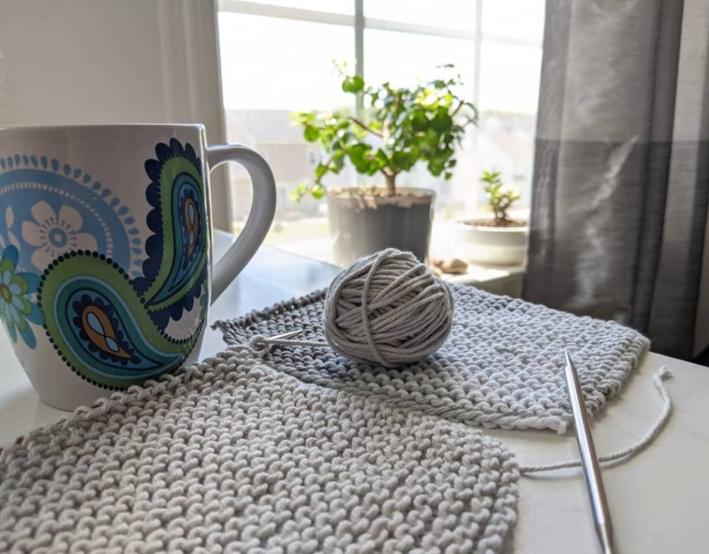 Grey cotton knitted washcloths in progress on a table, next to a painted coffee cup, in front of a sunny window with plants.