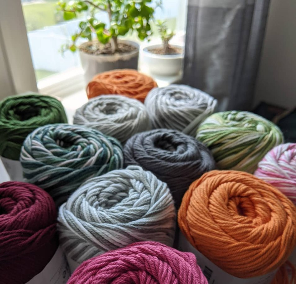 Colorful cotton yarn skeins arranged on a table in front of a sunny window with plants.