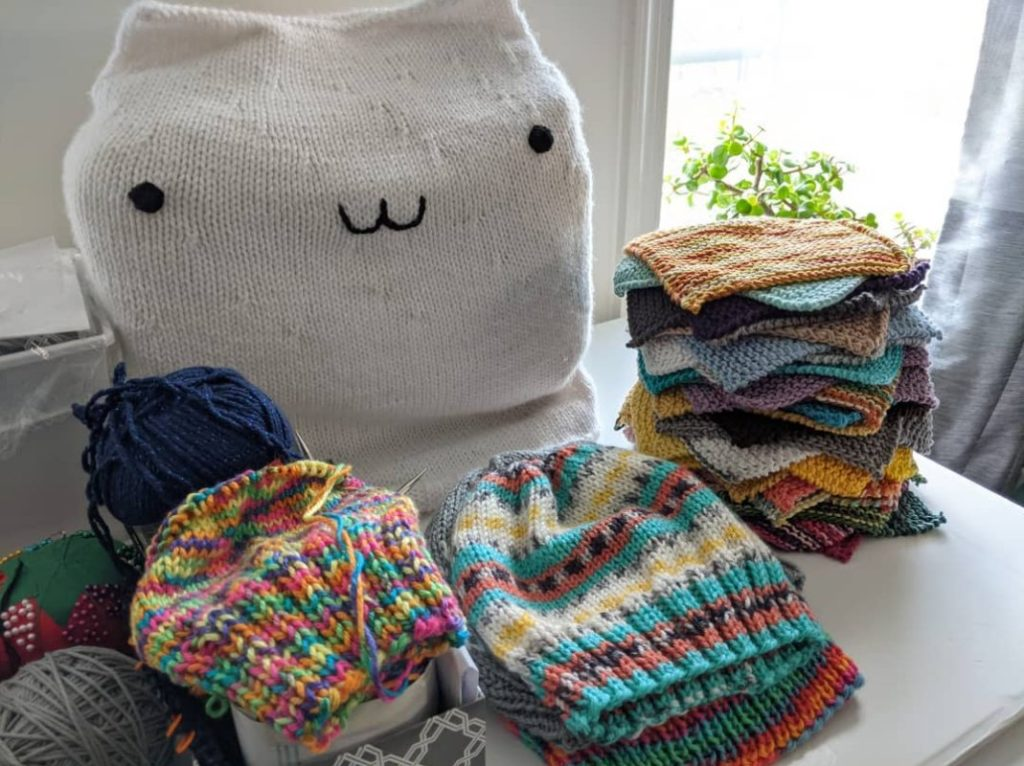Lots of colorful knitted items, some still in progress, sitting in piles on a table, in front of a sewing machine covered by a knitted Bongo Cat cover, with a sunny plant filled window in the background.