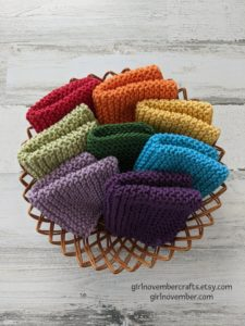 A low brown basket with 8 folded rainbow colored hand knit washcloths inside, atop a greyish wooden backdrop.
